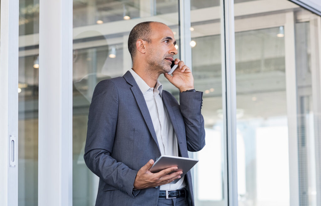Man talking on phone with tablet in his hand